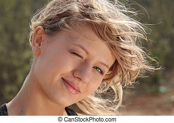 Blond fitness girl in wind portrait nature background
