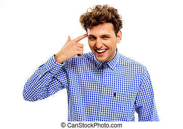 Portrait of a funny young man pointing finger gun gesture to...