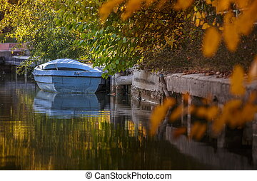 Old wooden blue boat moored on a lake bank under the trees...
