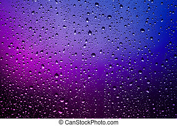 Raindrops on a window pane. Purple lights.