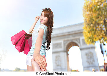 Happy Shopping in Paris - beautiful young woman holding...