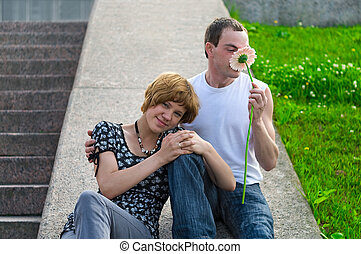 First Date - Teenager holds flower to girlfriend. They a on...
