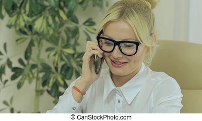 Gorgeous girl talking on mobile phone in office