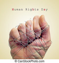man hand tied with wire and the text human rights day - a...