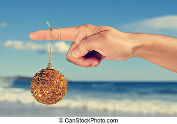 christmas on the beach - a golden christmas ball hanging in...