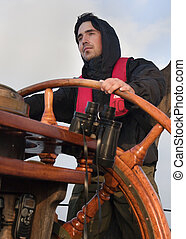 Young sailor steering tall ship - Young sailor on a ship's...