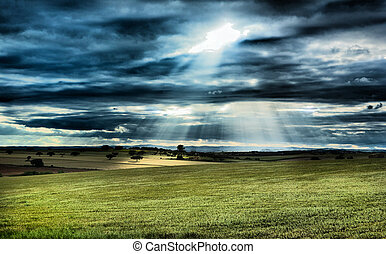 Rural landscape, dramatic sky, and sun rays light over...