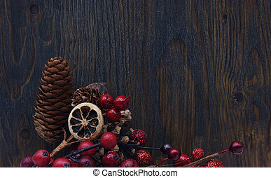 Christmas berries and pine cones on a wooden background