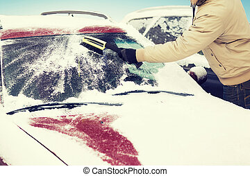 man cleaning snow from car windshield with brush -...