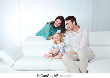 family looks happy - mom dad and daughter sitting on the...