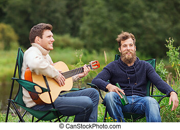 smiling tourists playing guitar in camping - adventure,...