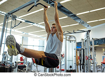 man flexing abdominal muscles on pull-up bar - sport,...