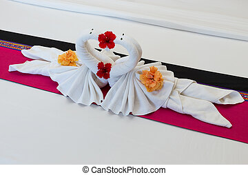 white swans made from towels on bed in the hotel