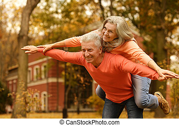 Mature couple in the autumn park - Mature couple having fun...