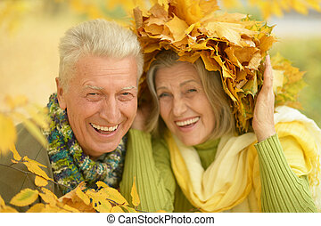 Old couple at autumn park - Happy old couple having fun at...