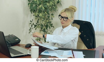 Business woman considers graphs and reports in office