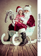 Christmas - Santa Claus and child sitting on sleigh...