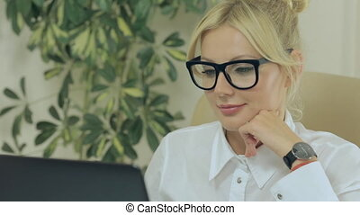 Girl smiling and looking at computer screen in office