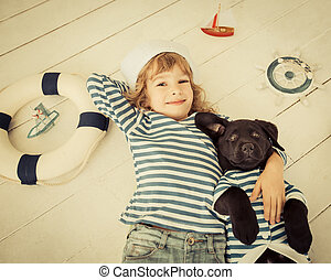 Child and dog - Happy kid dressed in sailor. Child playing...