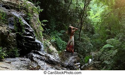 Young woman rises hands at waterfall in jungle Koh Samui....