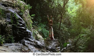 Young woman rises hands at waterfall in jungle Koh Samui...