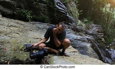 Caucasian tourist taking photos and videos of a waterfall in the mountains on Koh Samui. Thailand. HD. 1920x1080