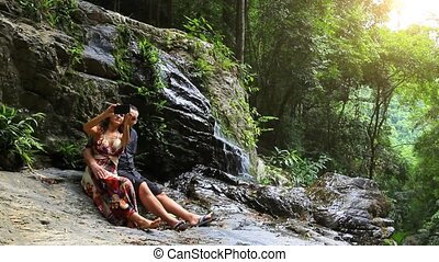 Couple having fun together outdoors. Taking self portrait with camera phone after hiking to incredible waterfall in Koh Samui. Thailand. HD. 1920x1080