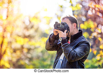 photographer with professional digital camera taking...