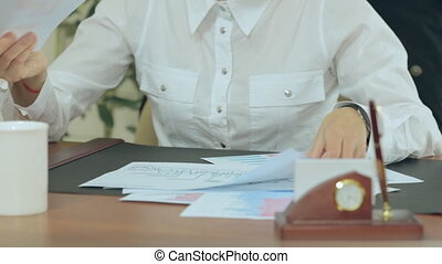 Close up of a girl working with documents in office