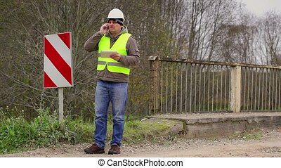 Engineer with cell phone near bridge defence barriers