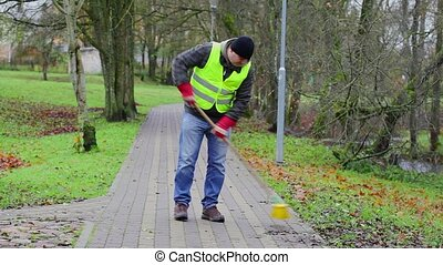 Worker sweeps leaves in the park