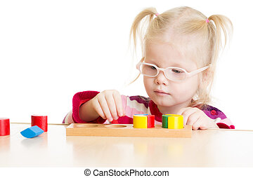 Kid in eyeglases playing logical game isolated on white