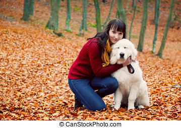 Young pretty woman hugging cute white puppy dog in autumn...