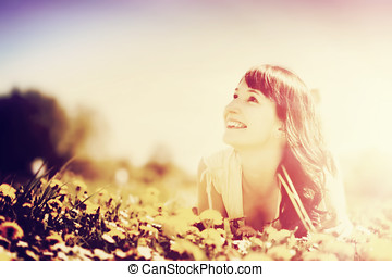 Young beautiful woman lying on grass full of spring flowers. Vintage style.