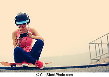 woman skateboarder listening music from cellphone mp3 player...