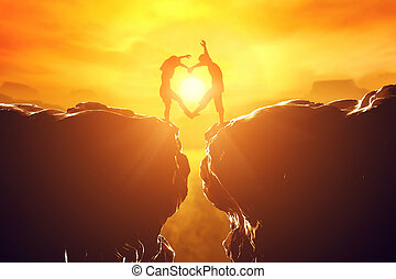 Happy couple in love making heart shape over precipice at...