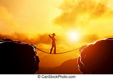 Man in hat walking, balancing on rope over mountains at...