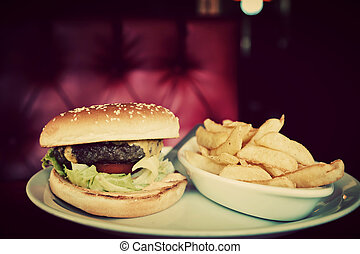 Hamburger and french fries plate in american food restaurant...