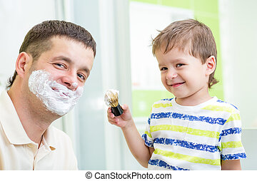 kid boy and father having fun in bathroom at shaving