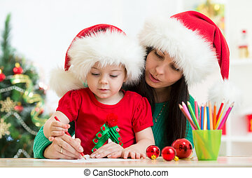 Child girl and mother writing christmas letter to Santa -...
