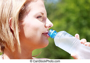 Pretty woman drinking water on the summer glade