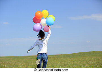 young asian woman with balloons - young asian woman jumping...