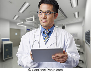 asian doctor - male asian doctor with tablet computer.