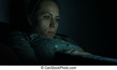 laptop in night - Woman lying with her laptop in night in...