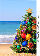 Christmas tree on the sand on the beach - Festive christmas...