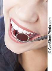 Examining Female Patient's Teeth Using Mouth Dental Mirror