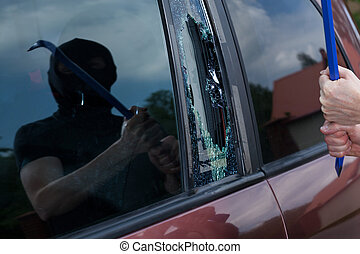 Car robber with crowbar - Horizontal view of car robber with...