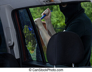 Burglar with crowbar breaking car window, horizontal