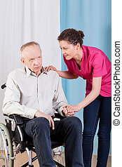 Nurse caring about disabled man on a wheelchair