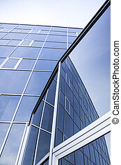 facade of office building and reflections of blue sky with...